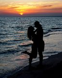 Couple silhouette on beach against sunset. Young couple silhouette on a sea beach on sunset background Royalty Free Stock Photo