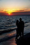 Couple silhouette on beach against sunset Stock Image