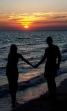 Couple silhouette on beach against sunset Stock Images