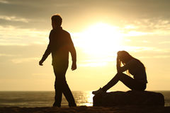 Couple silhouette breaking up a relation. On the beach at sunset Royalty Free Stock Images