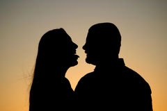 Couple Silhouette Flirt. Great and very fun silhouette of a man and woman at sunset. The woman sticks her tongue out at the man. Very flirtatious Stock Photo