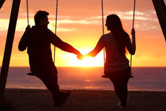 Couple silhouette holding hands watching a sunrise. Back light portrait of a couple silhouette sitting on swing holding hands watching a sunrise on the beach Stock Photo