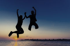 Couple silhouette jumping at sunset on the beach Stock Images