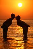 Couple silhouette kisses in sea on sunset Royalty Free Stock Photos