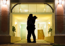 Couple in silhouette Kissing. In Front of Apartment Entrance Stock Photography