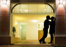 Couple in silhouette Kissing. In Front of Apartment Entrance Stock Image