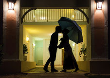 Couple in silhouette Kissing Under Umbrella. In Front of Apartment Entrance Stock Photo