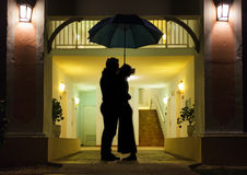 Couple in silhouette Kissing Under Umbrella. In Front of Apartment Entrance Royalty Free Stock Image