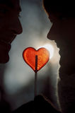 Couple silhouette in love hold heart shape lollipop Royalty Free Stock Photo