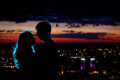 Couple silhouette at night city. Young couple silhouette hugging and looking at each other outdoors at night neon city background Royalty Free Stock Photos