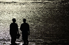 Couple in silhouette in shallow, romantic, shimmering ocean Stock Photography