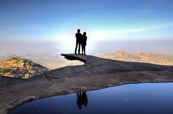 Couple silhouette on the edge of a cliff Royalty Free Stock Photo