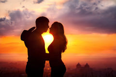 Couple silhouette at sunset. Young couple silhouette hugging and kissing outdoors at sunset background. Sun between them. Man with cowboy hat at his back Stock Photography