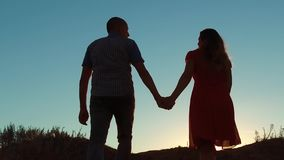 Couple silhouette walking holding hand toward the sun outdoors at sunset dramatic sky background. young happy couple go stock video