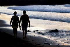 Couple silhouette walking at the seaside at sunset Royalty Free Stock Photography