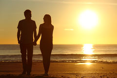 Couple silhouette walking together on the beach. Front view of a full body of a couple silhouette walking together on the beach at sunset in summer Stock Images