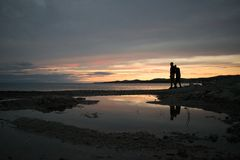 Couple silhouettes on a beach royalty free stock photo