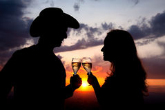 Couple Silhouettes clanging glasses at sunset Stock Images