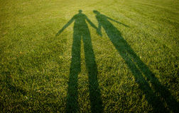 Couple silhouettes on grass Royalty Free Stock Images