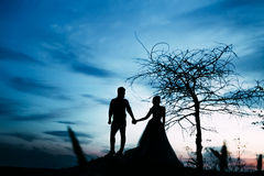 A couple of silhouettes holding hands and stands together looking each other in a date at sunset. Artwork. Front view Stock Photo