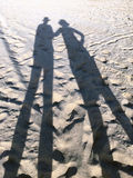 Couple silhouettes on the sand Stock Image