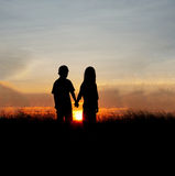 Couple silhouettes at sunset. Front view of a full body of couple silhouettes holding hands and walking together looking each other in a date at sunset on the Royalty Free Stock Photography