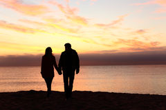 Couple silhouettes walking together at sunset Stock Images