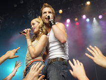 Couple Singing In Front Of Adoring Fans. Young men and women singing on stage in concert in front of adoring fans Stock Image