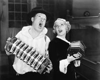 Couple singing while playing two accordions Stock Photos