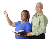 Couple Sings Praises. A senior African American couple singing praises together from a hymnal.  On a white background Royalty Free Stock Photography