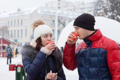 Couple sipping hot drinks in a wintry town square Royalty Free Stock Photo