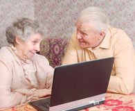Couple sit ar the laptop and discuss Royalty Free Stock Photography
