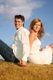 Couple sit back to back Stock Image
