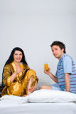 Couple sit on bed drinking orange juice Royalty Free Stock Images