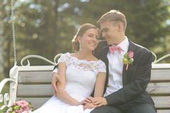Couple sit on bench in park. Wedding shot of bride and groom sit on bench in park Stock Image