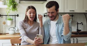 Couple celebrating unexpected great news received by smartphone sms