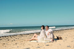 Couple sit down on the beach Stock Images