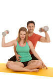 Couple sit flex weights looking Stock Images