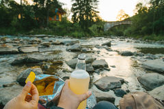 Couple sit near mountain river with chips and beer Stock Image
