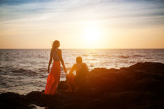 Couple Sit On The Rock And Wait For Sunset Stock Photo