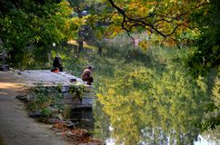 Couple sit quietly on jetty and fish at a lake outside Beijing China. Beijing, China - October 19, 2015: A man and woman sit motionless at separate ends of a Royalty Free Stock Images