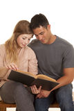 Couple sit reading a book together Stock Photos
