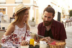 Couple sit reading guidebook outside a cafe, Ibiza, Spain stock images