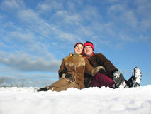 Couple sit on snow. Blue sky royalty free stock photography
