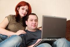 Couple sit on sofa and looking at laptop screen Stock Photography