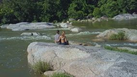 Couple Sit on Stone Hug Watch River against Jungle stock video