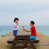 Couple sit together at the table near the beach Stock Image