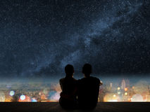 Couple sit under strars. Silhouette of young Asian couple sit on wooden ground above the city under stars Stock Image