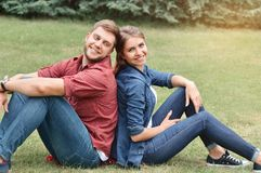 Couple siting back in back in the park Stock Photo