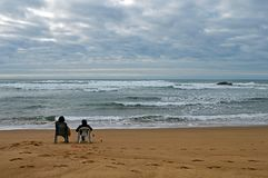 A couple siting on the beach Praia de Odeceixe in South Portugal royalty free stock photos